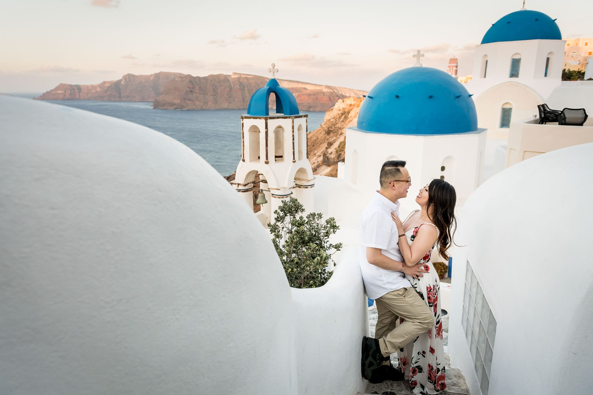 Santorini Honeymoon photo session image with a couple embracing on very unique set of white stairs with the three blue domes of Santorini in the background