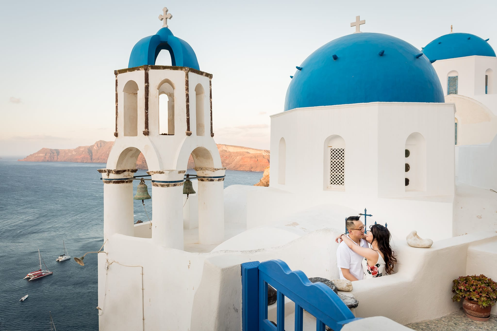 Santorini Honeymoon photo of a couple cuddling close with the three blue domes of Santorini in the background, along with the Aegean Sea