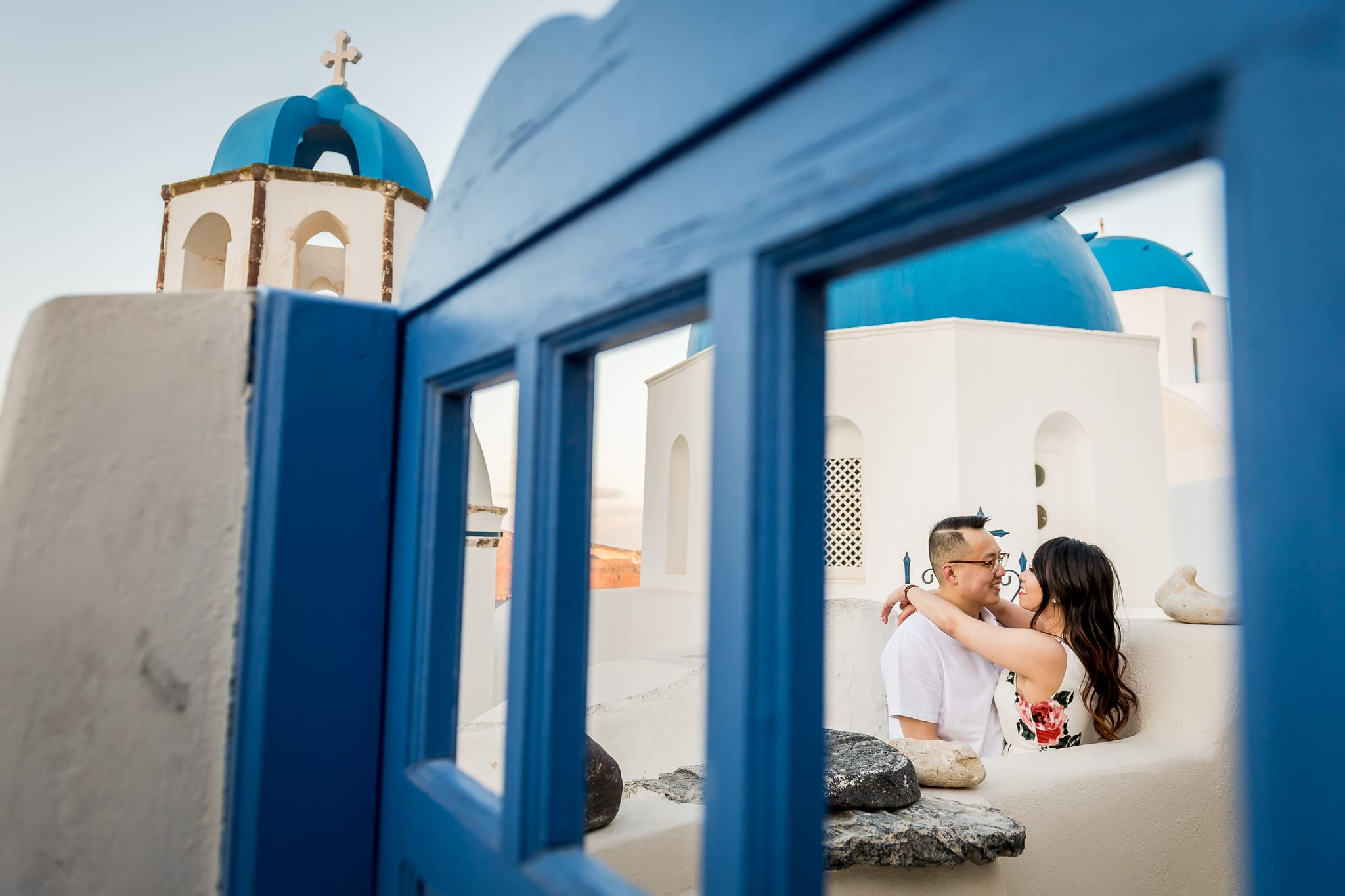 Santorini Honeymoon photo of a couple cuddling close, shot through a beautiful blue gate with the three blue domes of Santorini in the background