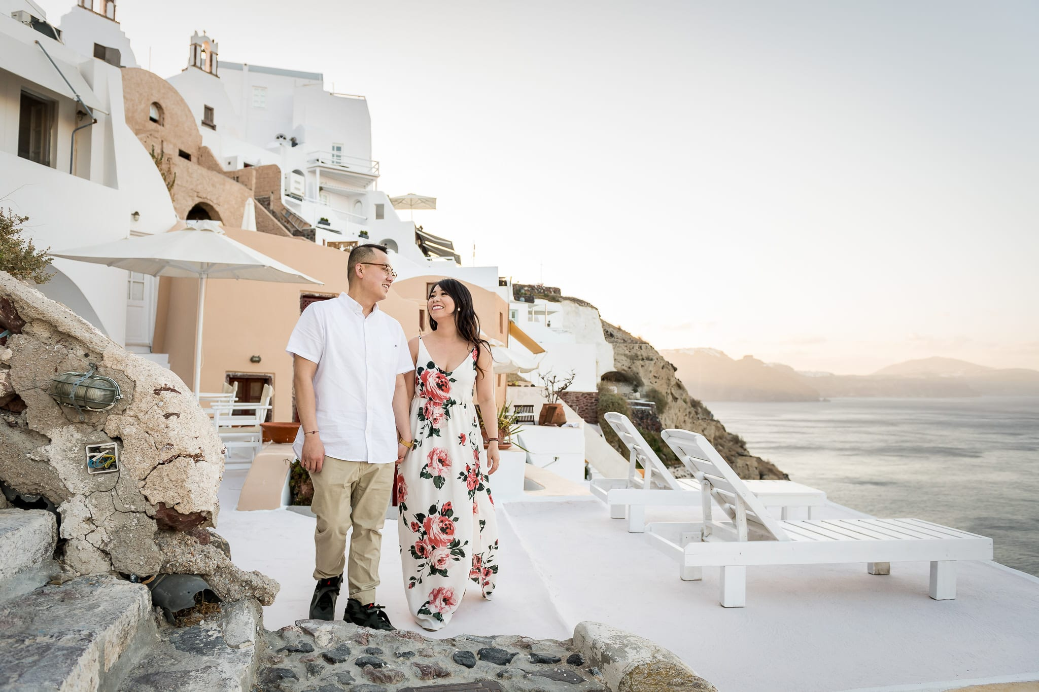 Couple holding hands on their honeymoon, overlooking the Aegean Sea at sunrise on Santorini