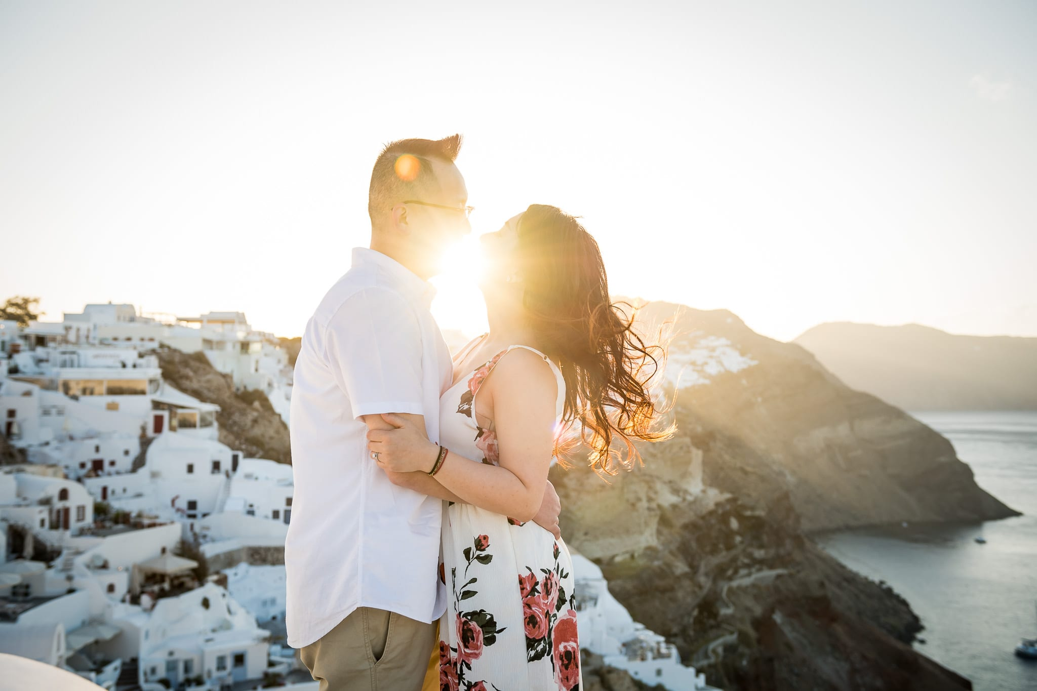 Sunrise light flare right between the kissing lips of this honeymooning couple overlooking the cliffs of Oia on the greek island of Santorini