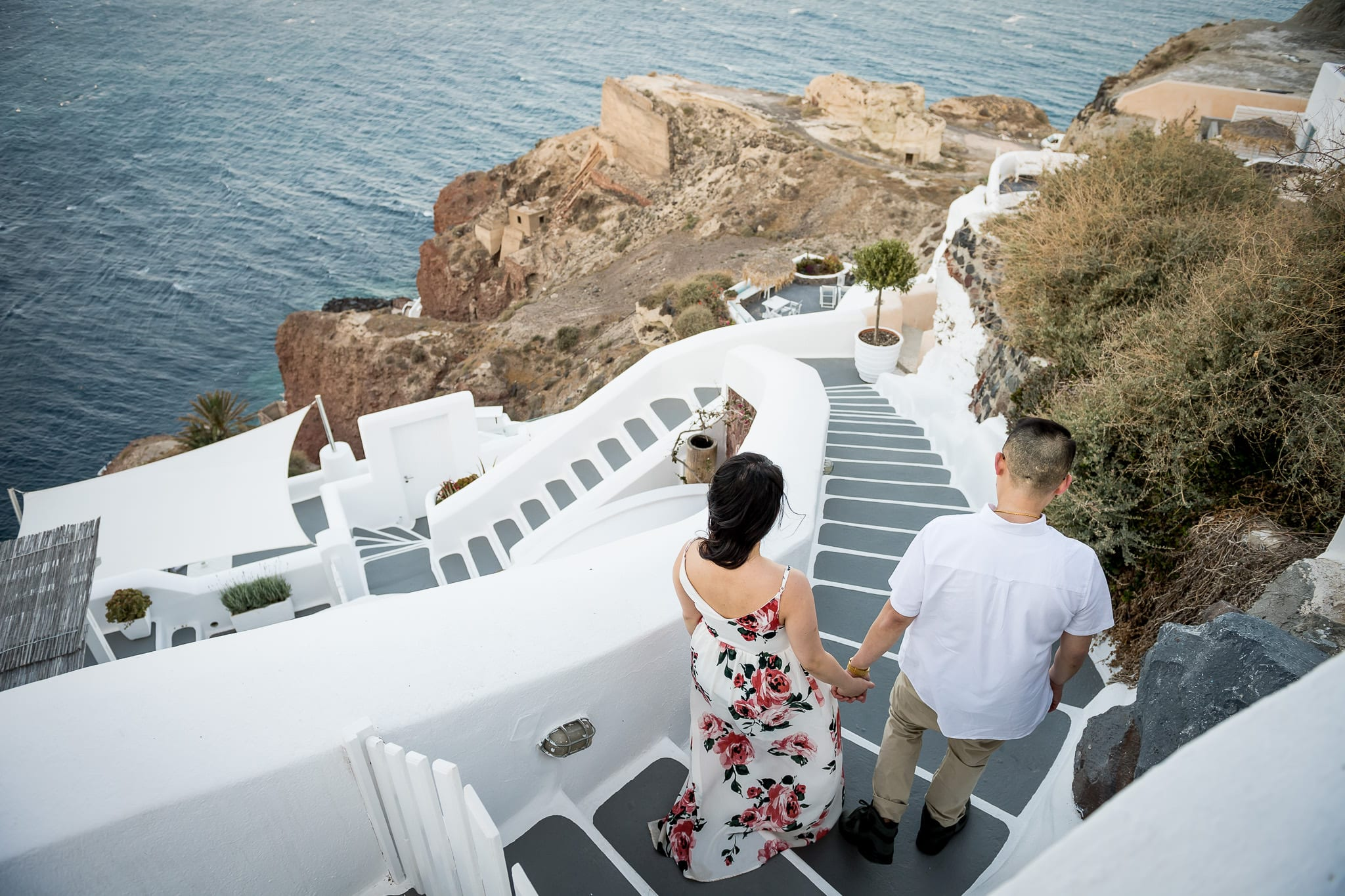 Santorini Honeymoon photo session image of a couple walking down a winding, bright white and gray steps on the cliffs of Oia