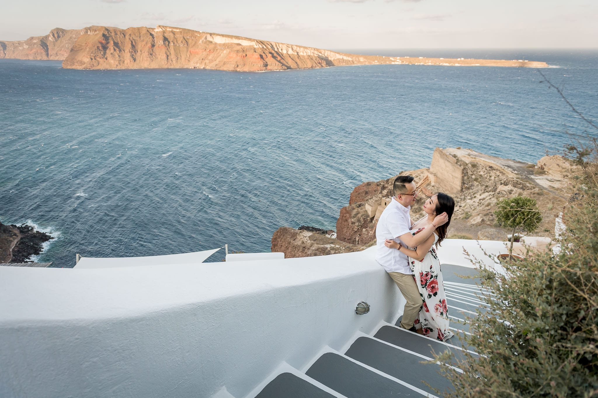 Couple cuddling closely along unique and winding, bright white & gray stairs, on the cliffs of Oia overlooking the Aegean Sea on their Honeymoon