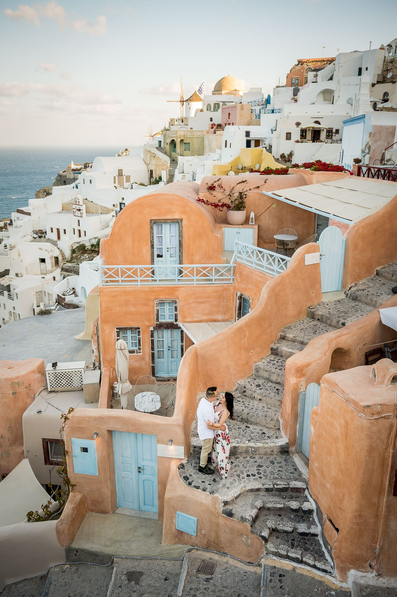 Newlywed couple embracing on the stairs of the Kastro Oia Houses on the greek island of Santorini