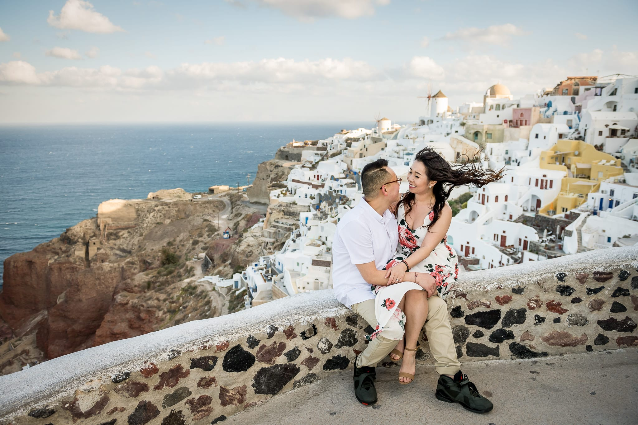 Newlywed bride sitting on her new husbands lap, along a stone wall of the Oia Castle, high above the colorful Santorini island village of Oia, with the iconic windmill in the background on their Honeymoon