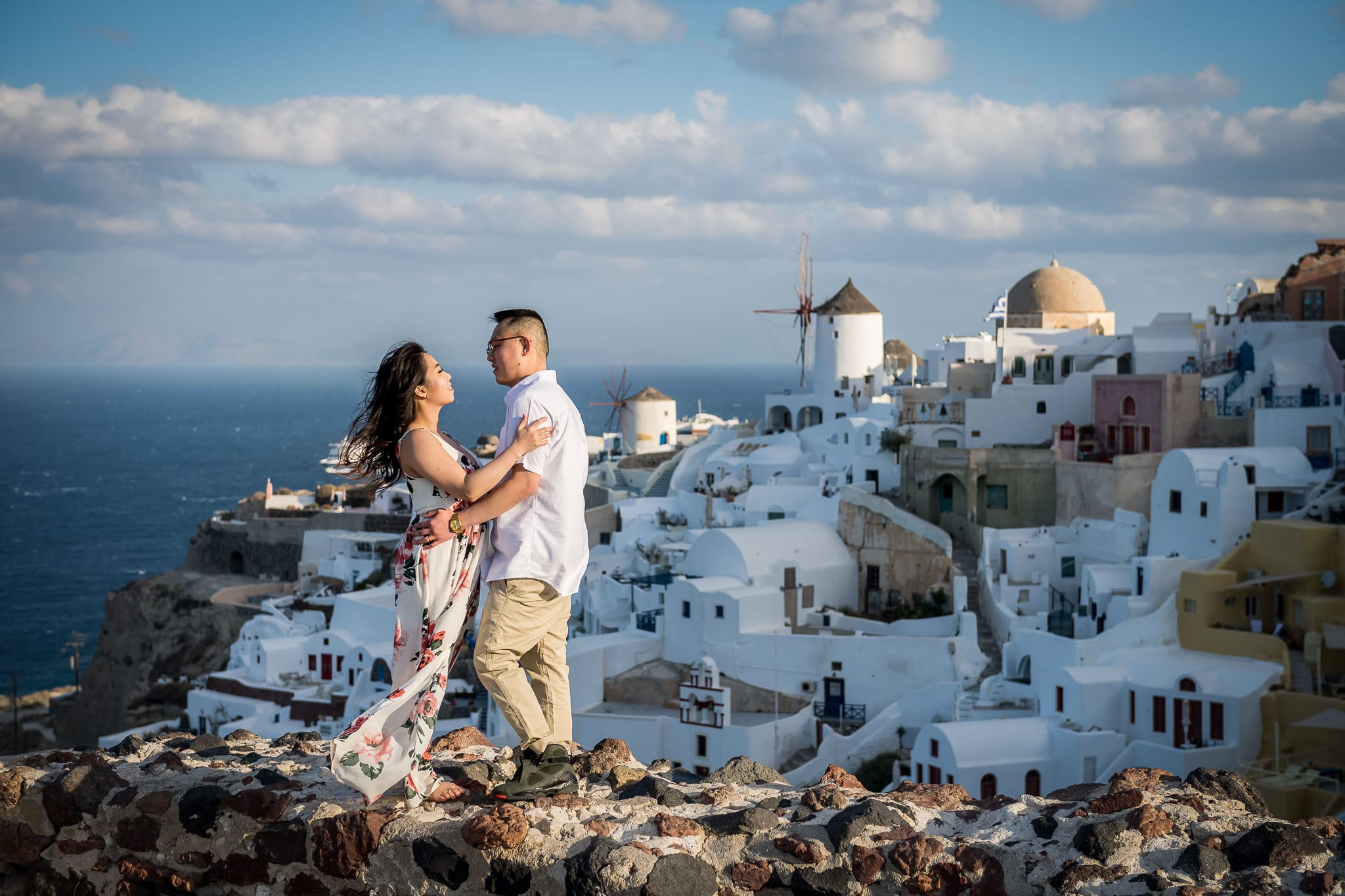 Honeymoon couple standing on a stone wall of the Oia Castle, during sunrise, high above the colorful Santorini island village of Oia, with the iconic windmill in the background
