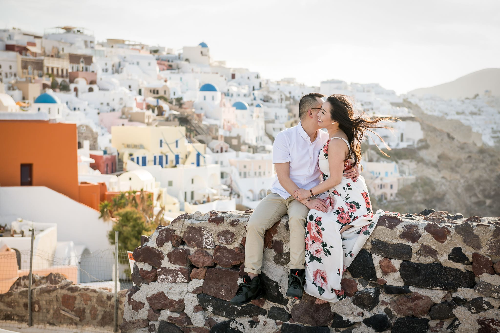 Honeymoon couple sitting on a stone wall of the Oia Castle, high above the colorful Santorini island village of Oia