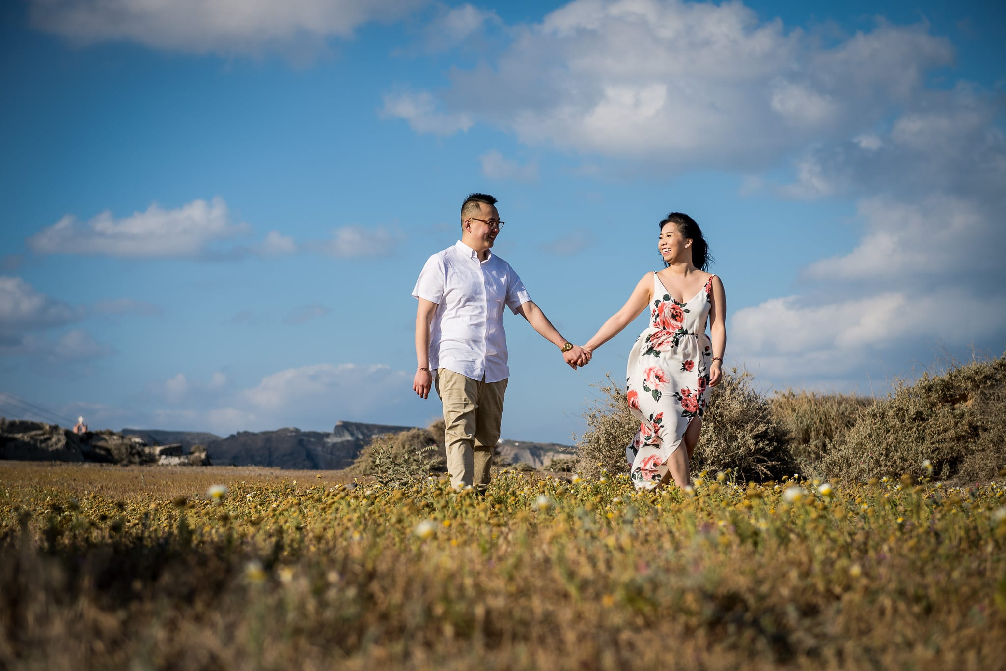 Newlywed couple holding hands and walking together under a bright blue sky, with puffy clouds, in a small prairie just outside the village of Oia