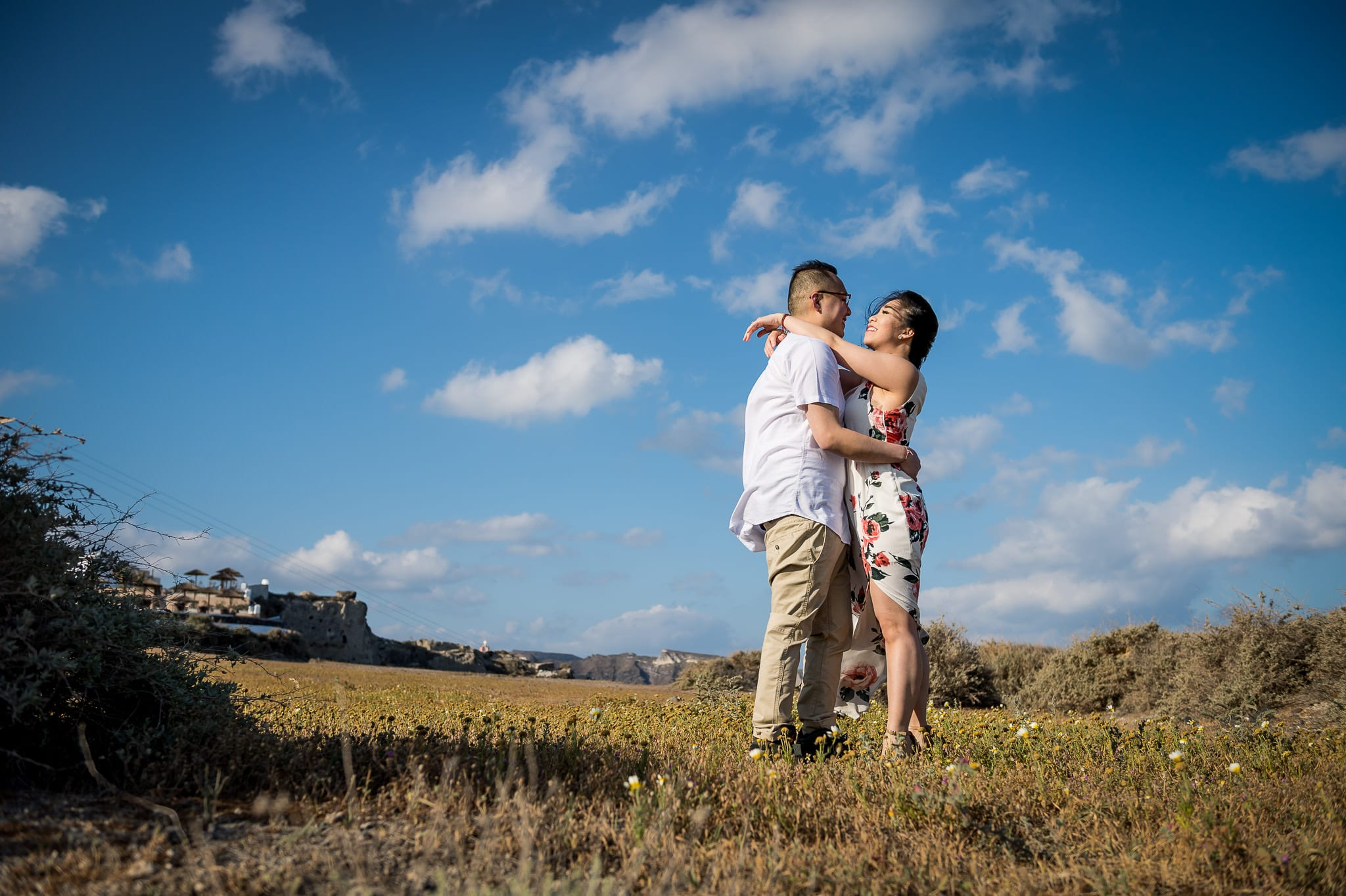 Image of a newlywed couple holding each other closely under a bright blue sky, with puffy clouds, in a small prairie just outside the village of Oia