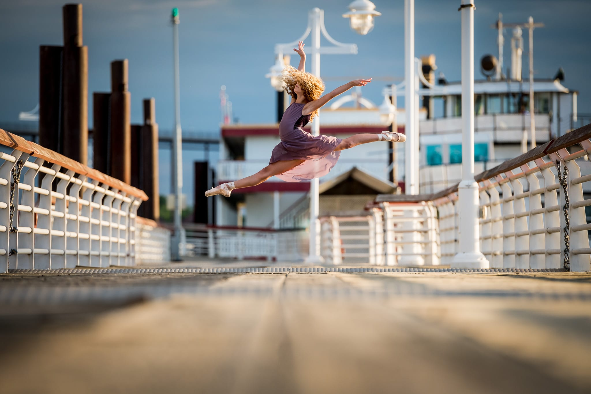 A young ballet dancer leaping into the air on the boat docks at Harriet Island
