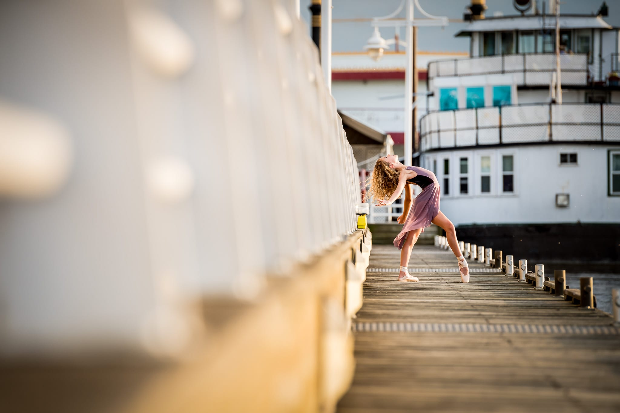A young ballerina dancer in a back bend on the boat docks at Harriet Island