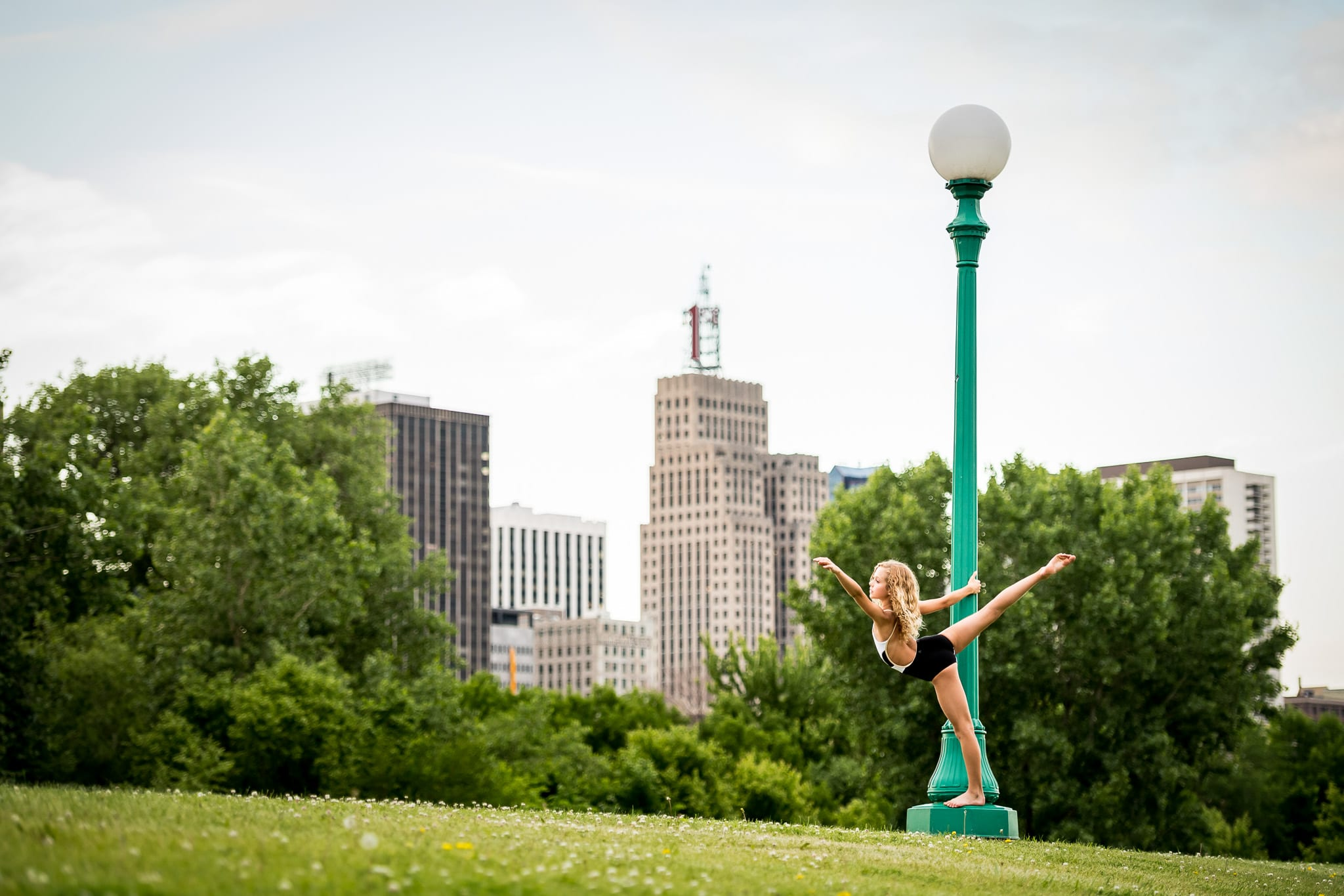 Young girl in a contemporary dance pose, hanging onto a green light post, with the downtown Saint Paul, MN skyline in the background.