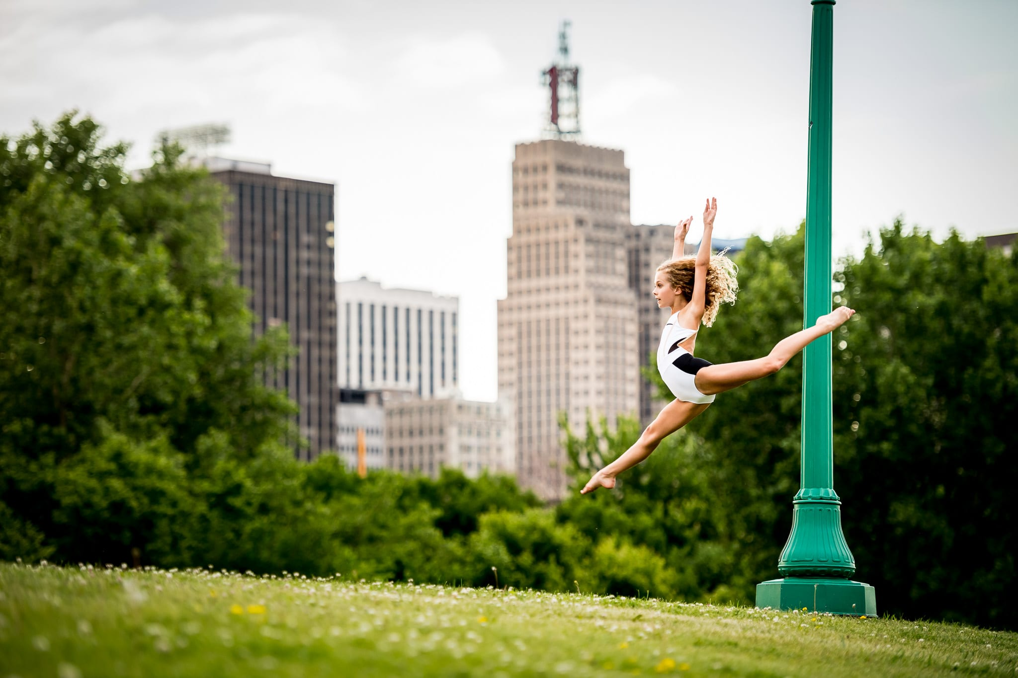 A young contemporary dancer leaping near a bright green light post, with the downtown Saint Paul, MN skyline in the background.