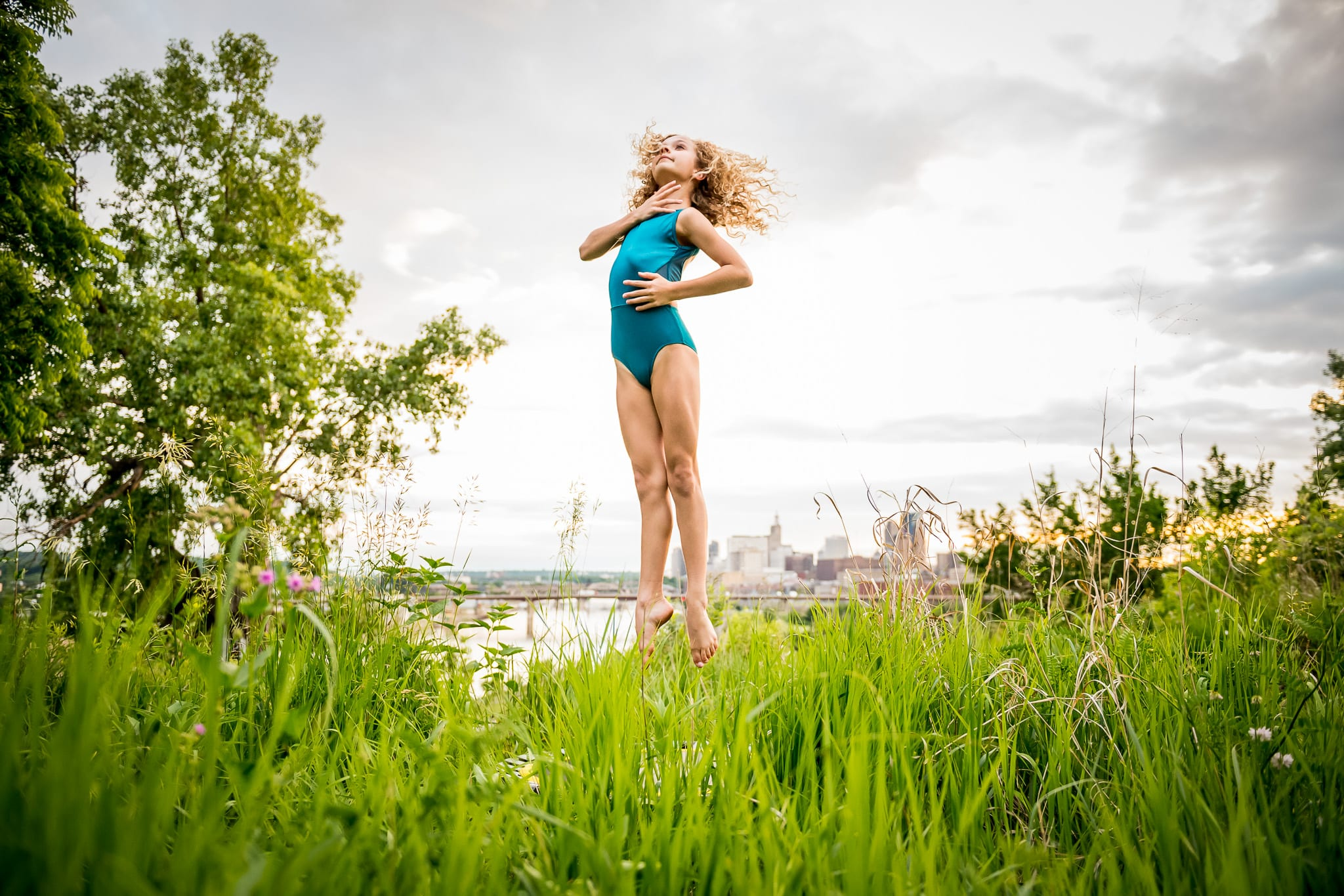 A young contemporary dancer jumping over the long grasses at Indian Mounds Park, with the downtown Saint Paul, MN skyline and the Mississippi River in the background.