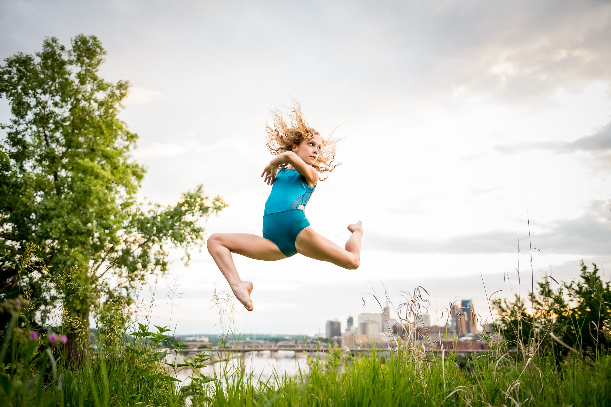 Contemporary dancer jumping and posing in the long grasses of Indian Mounds Park, with the downtown Saint Paul, MN skyline and the Mississippi River in the background.