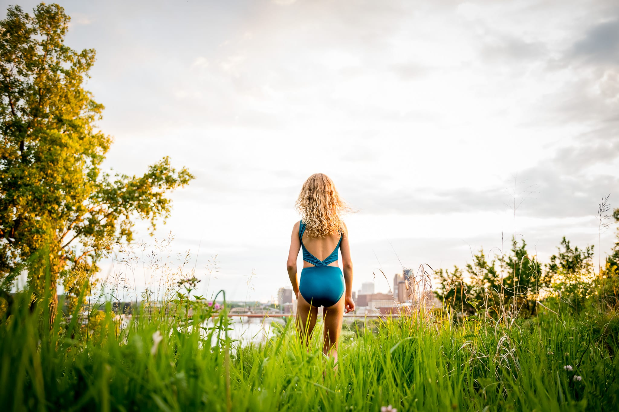 A young contemporary dancer standing in the long grasses of Indian Mounds Park at sunset, looking out from the beautiful overlook with views of downtown Saint Paul, MN skyline and the Mississippi River in the background.