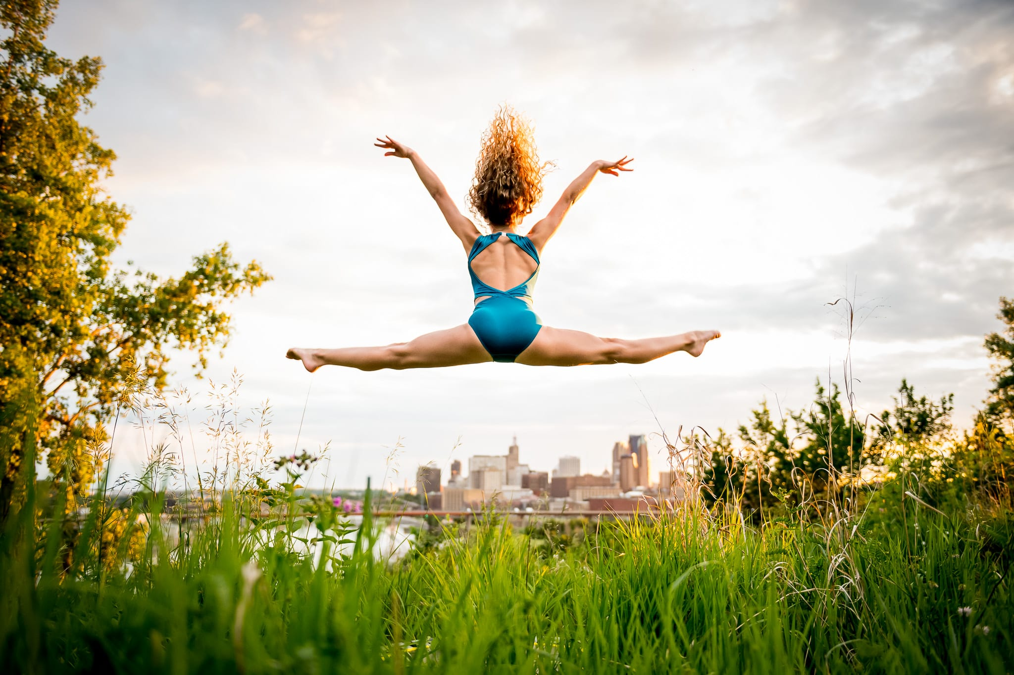 Saint Paul dance photo of a young contemporary dancer leaping into the air, overlooking the Mississippi River and downtown Saint Paul, MN