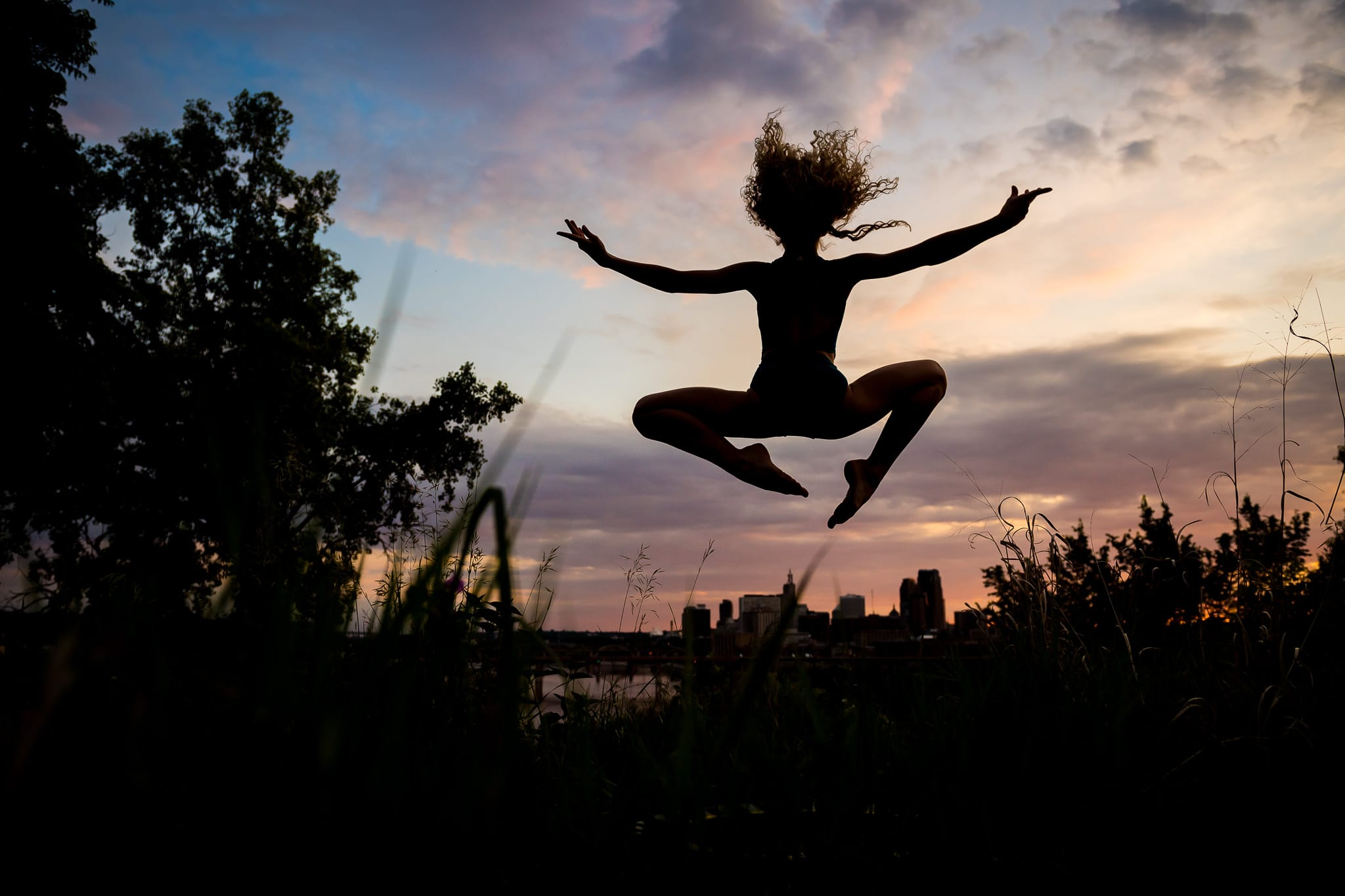 A young contemporary dancer leaping in silhouette at Indian Mounds Park in St. Paul, MN during sunset