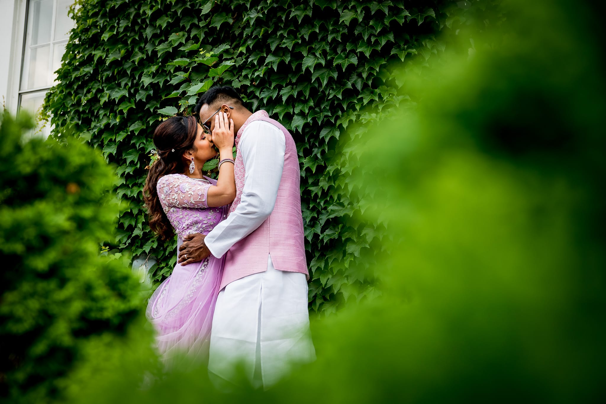 Traditionally dressed Indian couple share a kiss in front of the ivy wall at The Blaisdell during their wedding reception