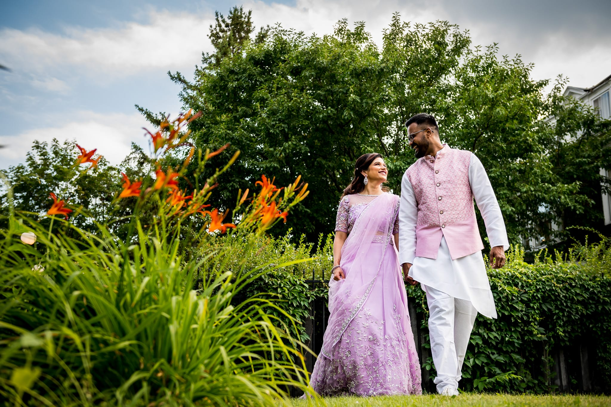 Traditionally dressed Indian couple walk along the beautifully landscaped grounds of the The Blaisdell during their wedding reception