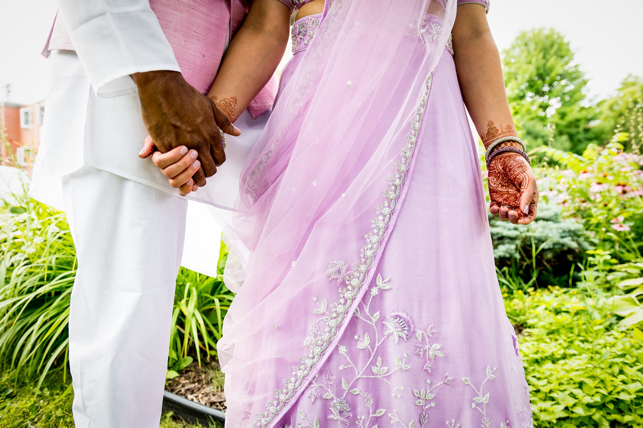 Traditionally dressed Indian couple hold hands, which are decorated in henna, on the grounds of the The Blaisdell during their wedding reception in Minneapolis