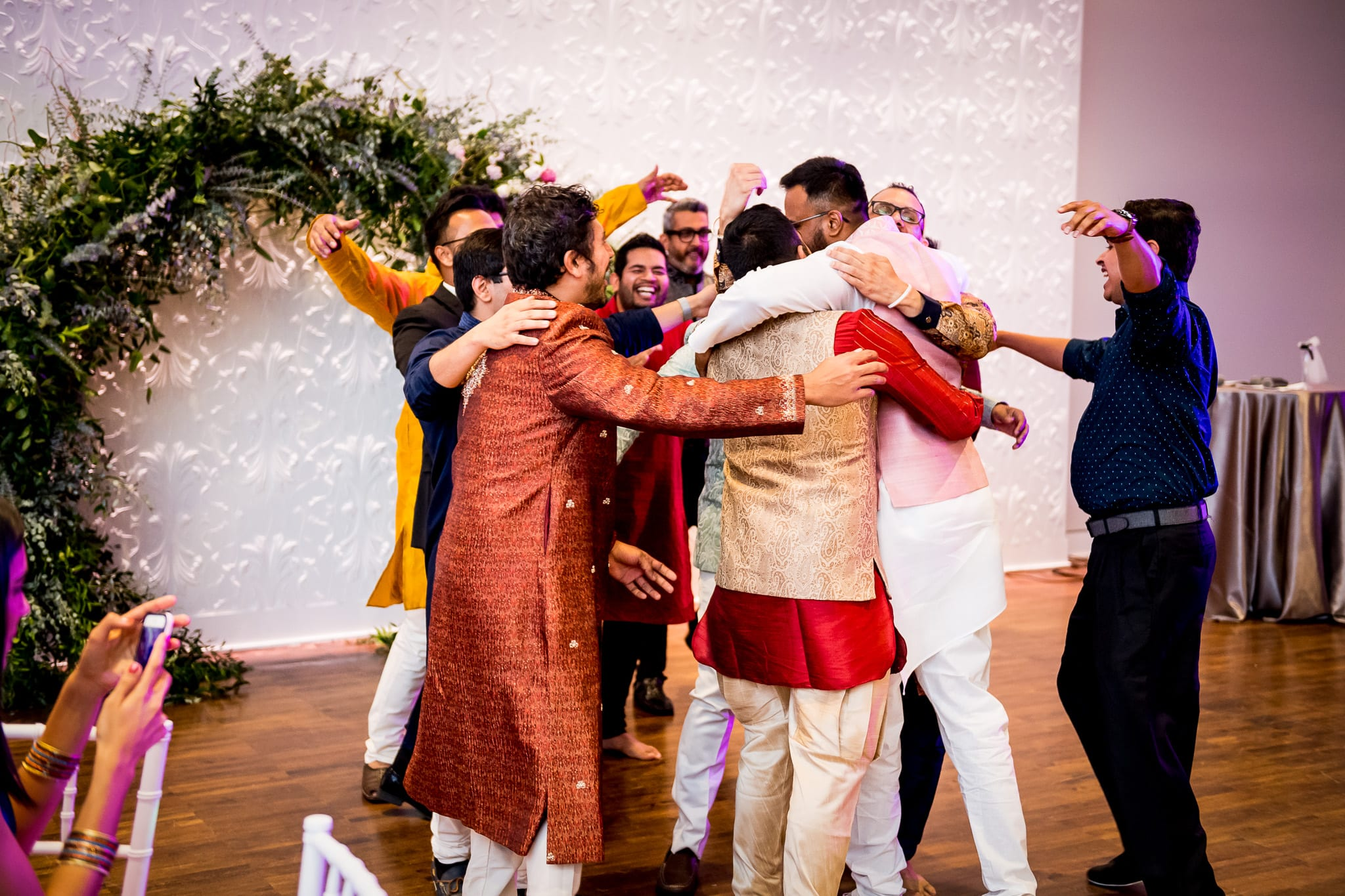 Groom getting a huge group hug from all of his groomsmen