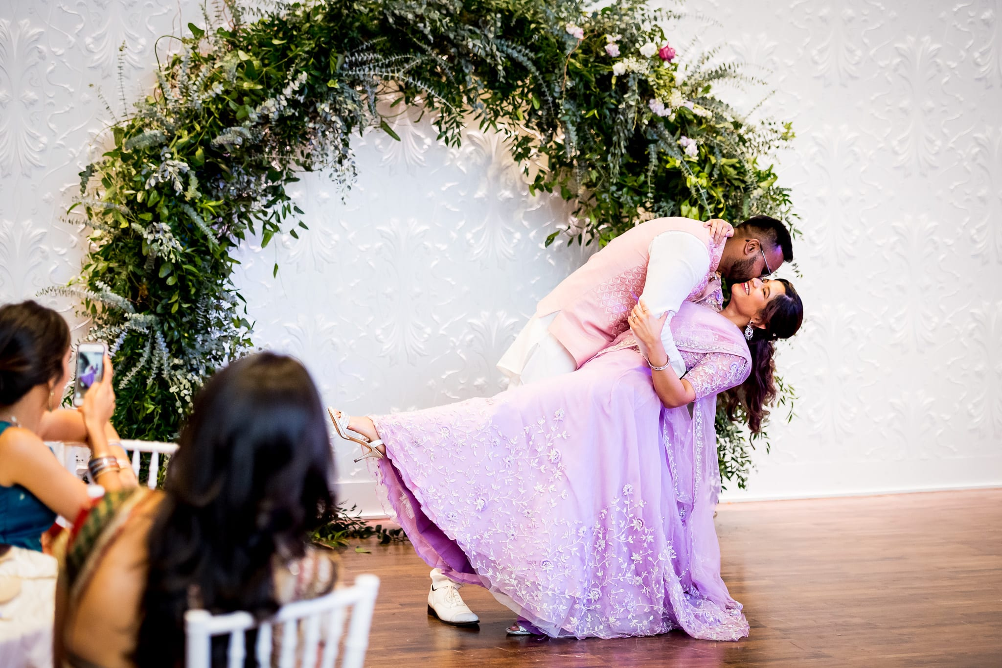 Groom dips the bride and gives her a kiss in front of the large white wall at The Blaisdell