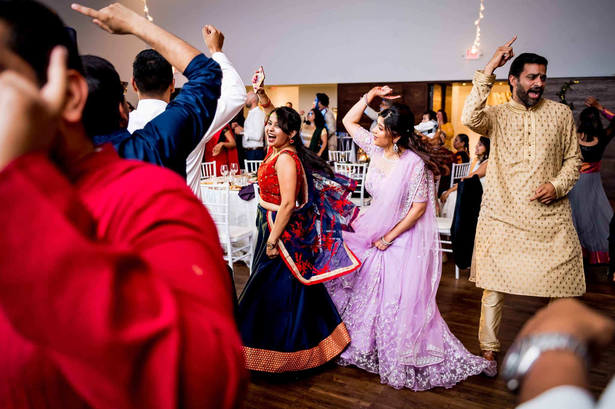 Wedding guests passionately dancing with bride during wedding reception at The Blaisdell