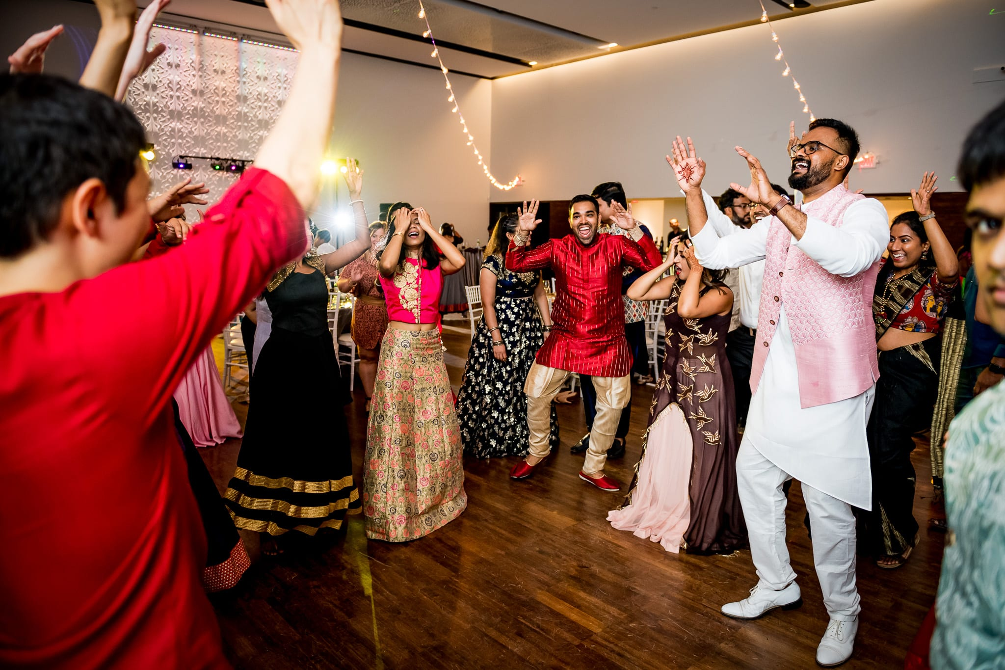 Wedding guests passionately dancing with groom during wedding reception at The Blaisdell
