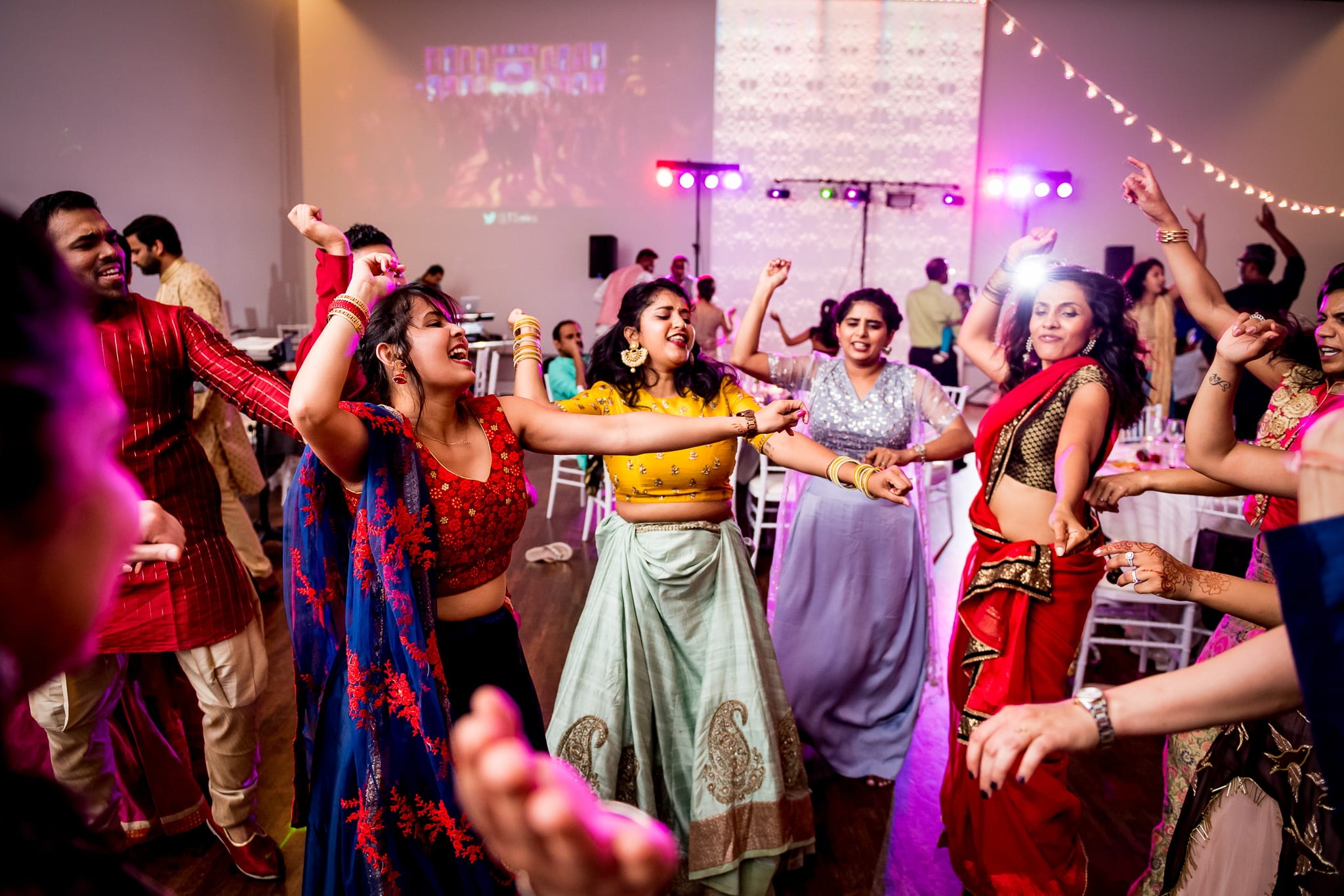 Many wedding guests dancing with their hands in the air during wedding reception at The Blaisdell