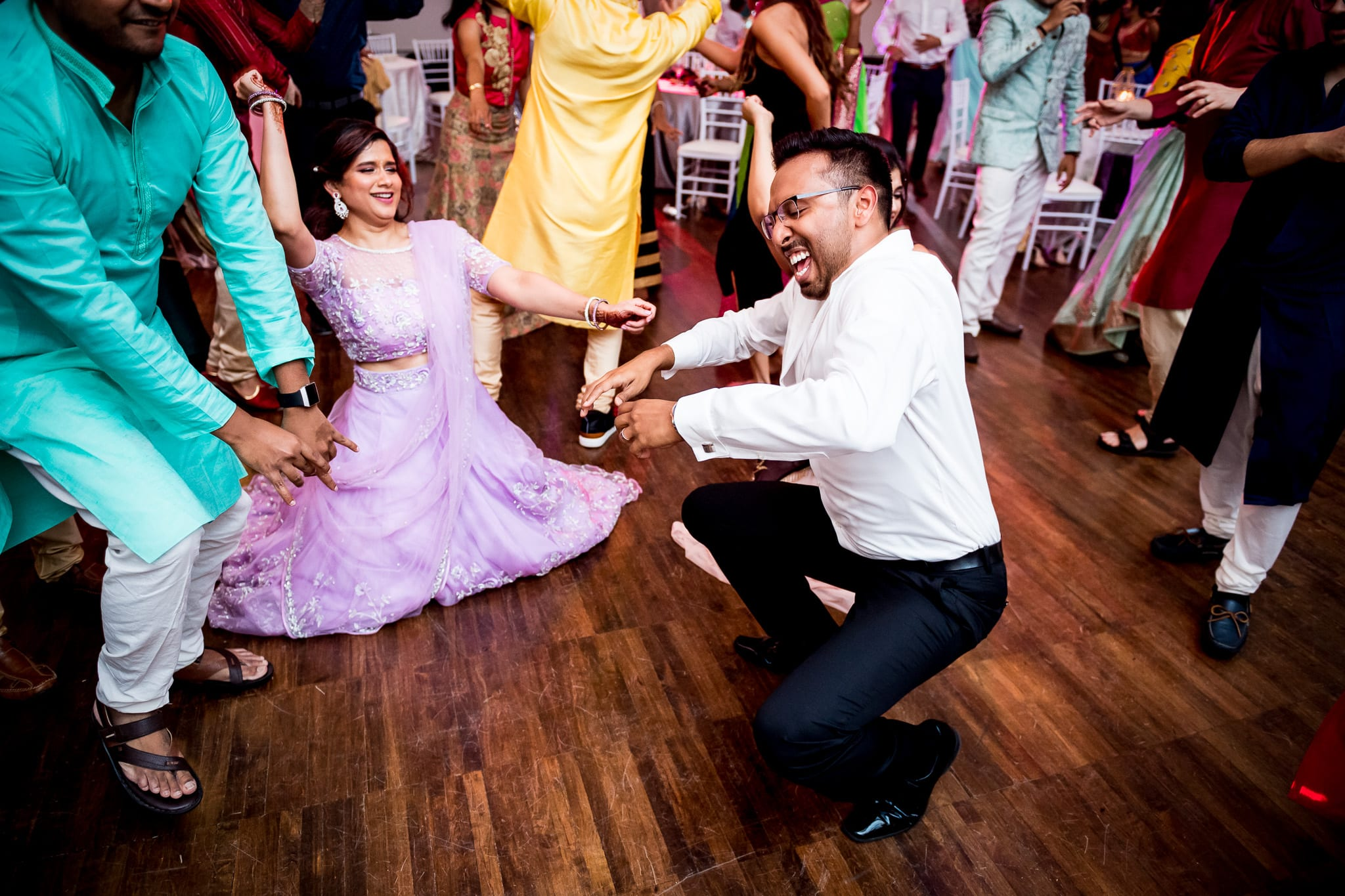 Wedding guests dance low to the ground with the bride