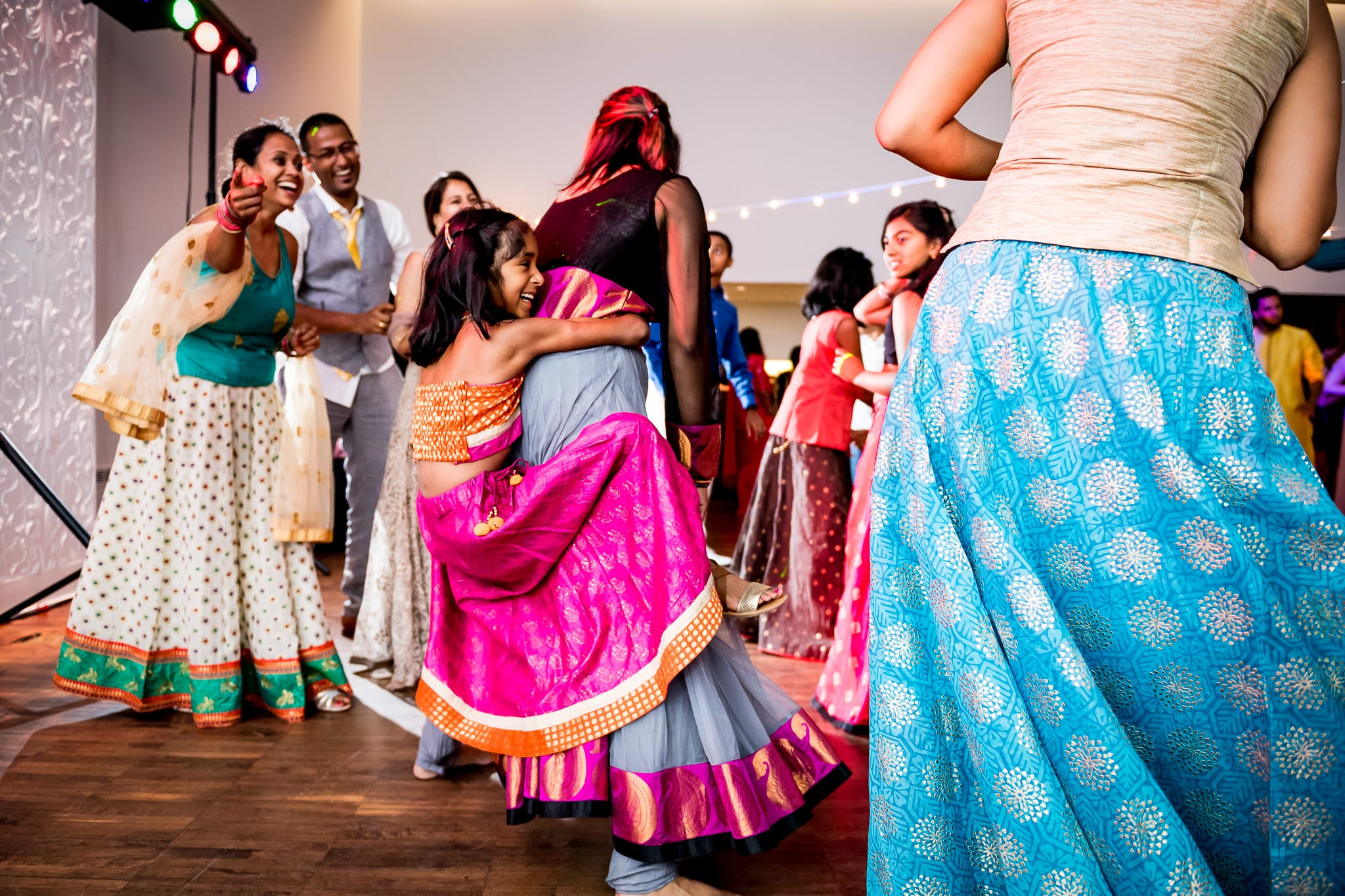 Junior bridesmaid hangs playfully on her mother, on the dance floor