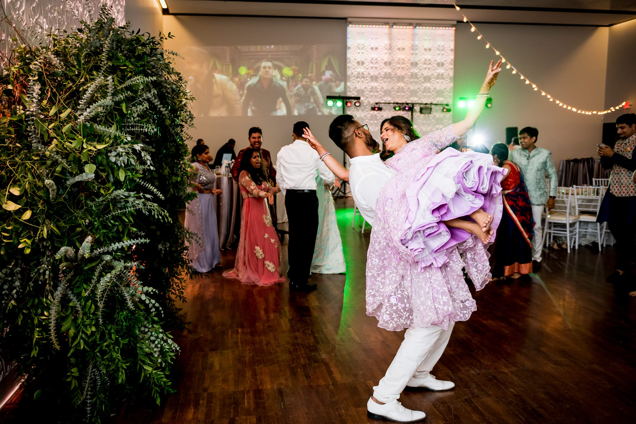 Groom picks up his bride and twirls her around
