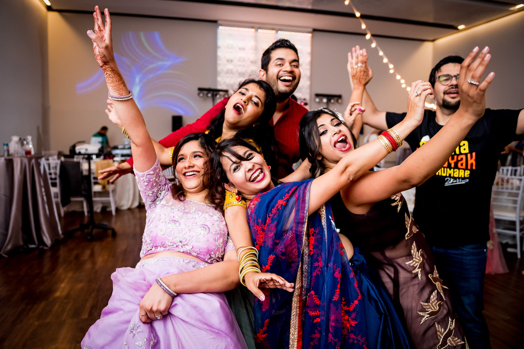 Wedding guests pose with the bride while dancing