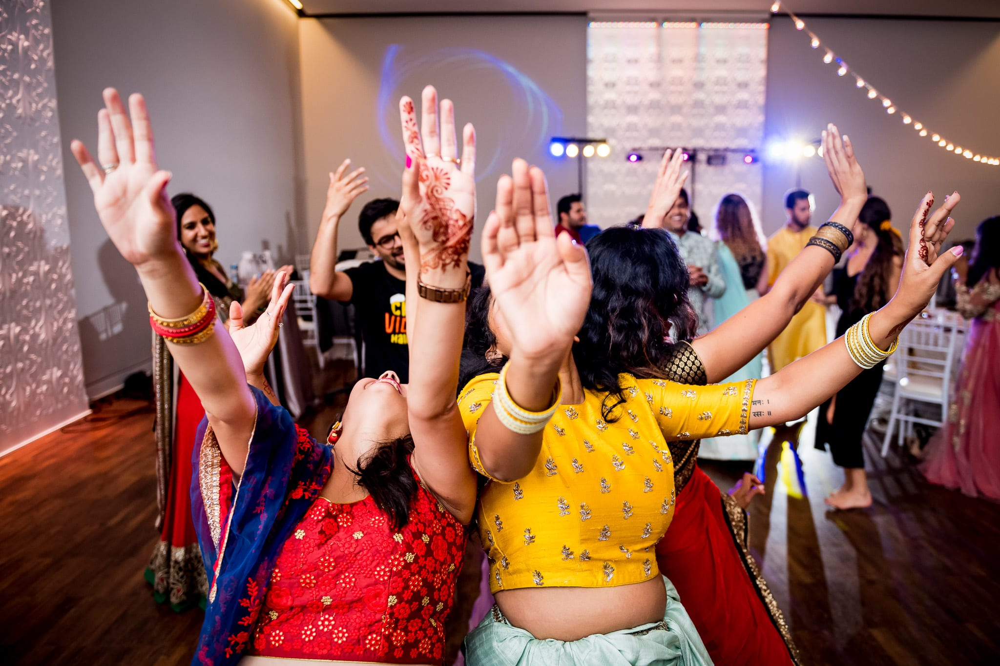 Colorfully dressed wedding guests leaning way back together on the dance with with their arms raised high into the air