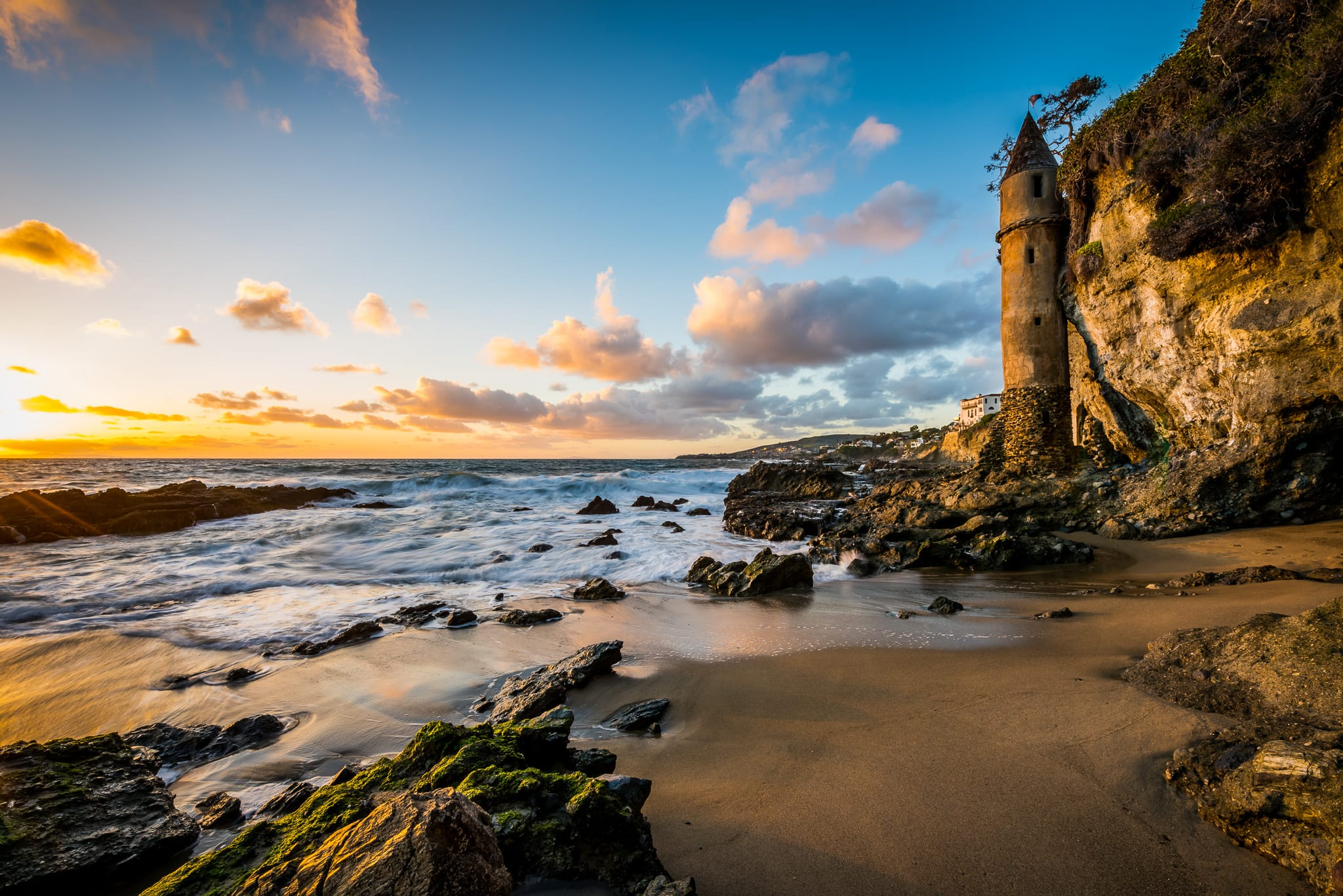 Long exposure wide angle landscape photo of Pirate Tower at Victoria Beach in Laguna Beach, during a colorful sunset sky