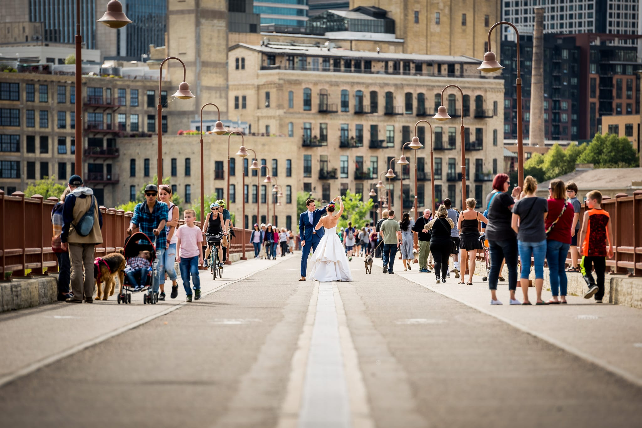 Groom twirls his bride to be in the middle of the Stone Arch Bridge