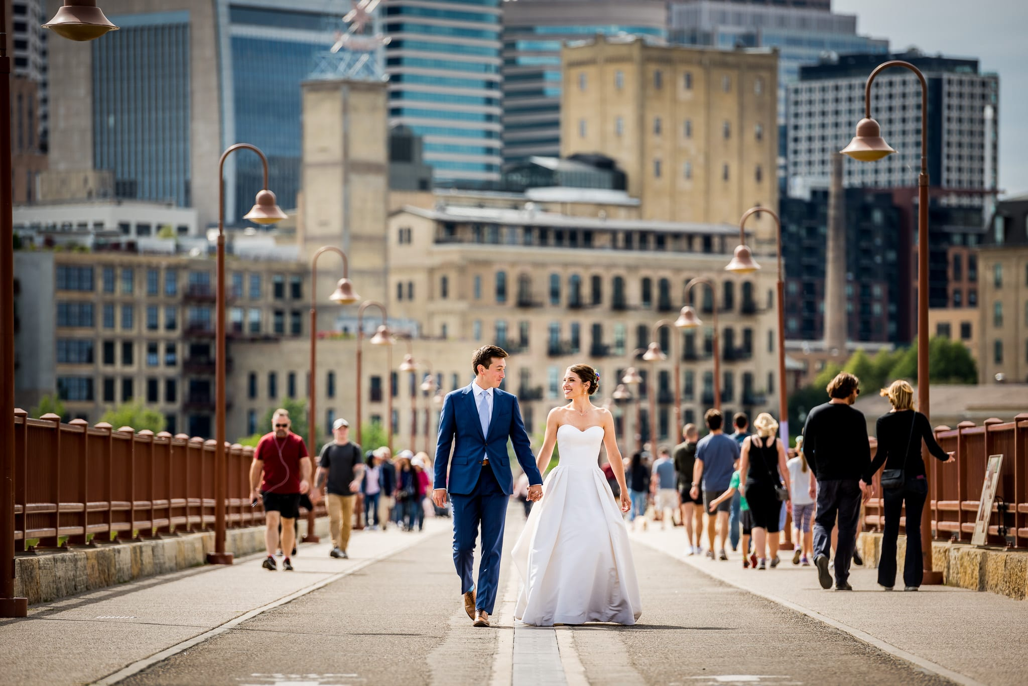 Couple holds hands and walks along the Stone Arch Bridge on their wedding day
