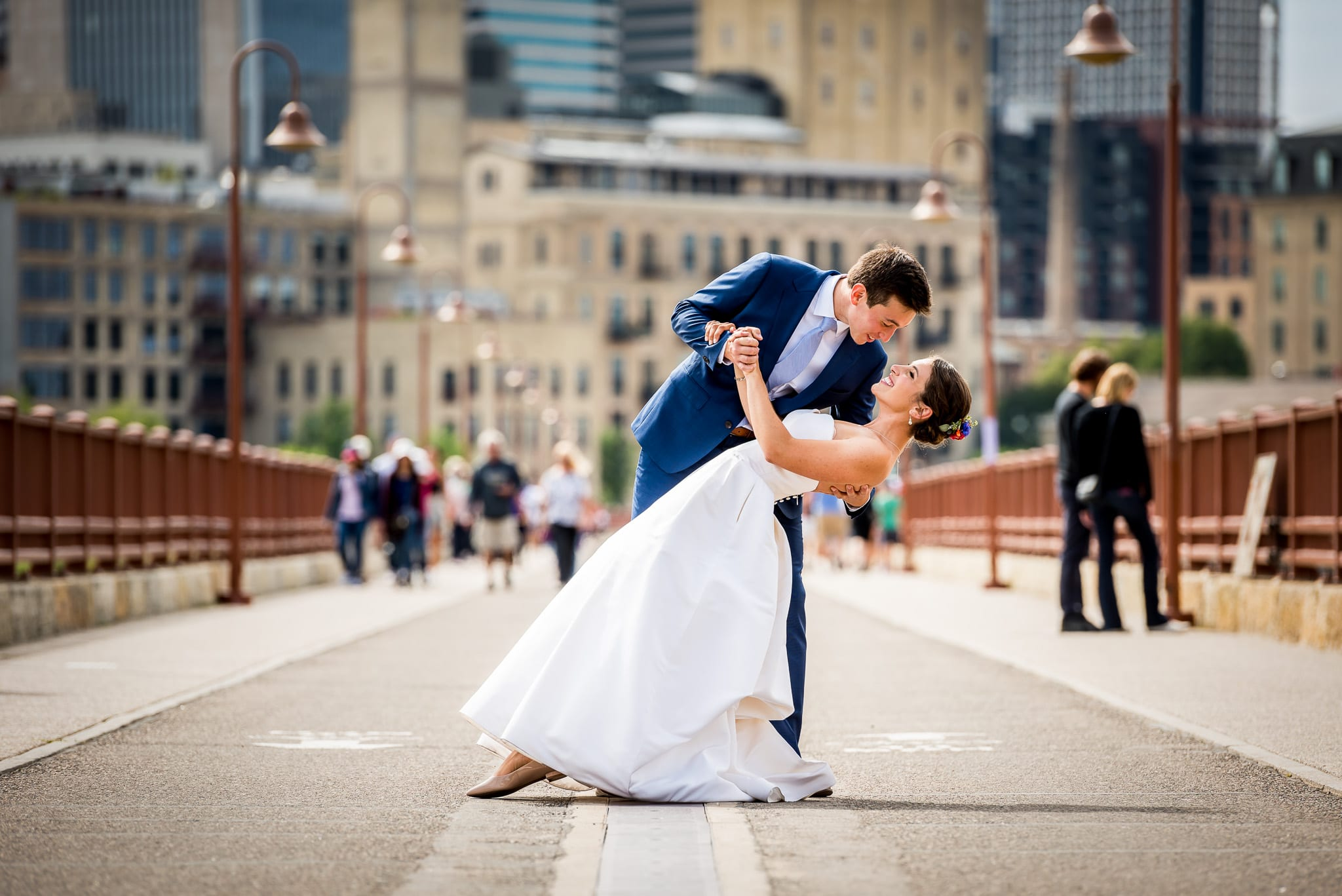 Groom dips his bride on the Stone Arch Bridge