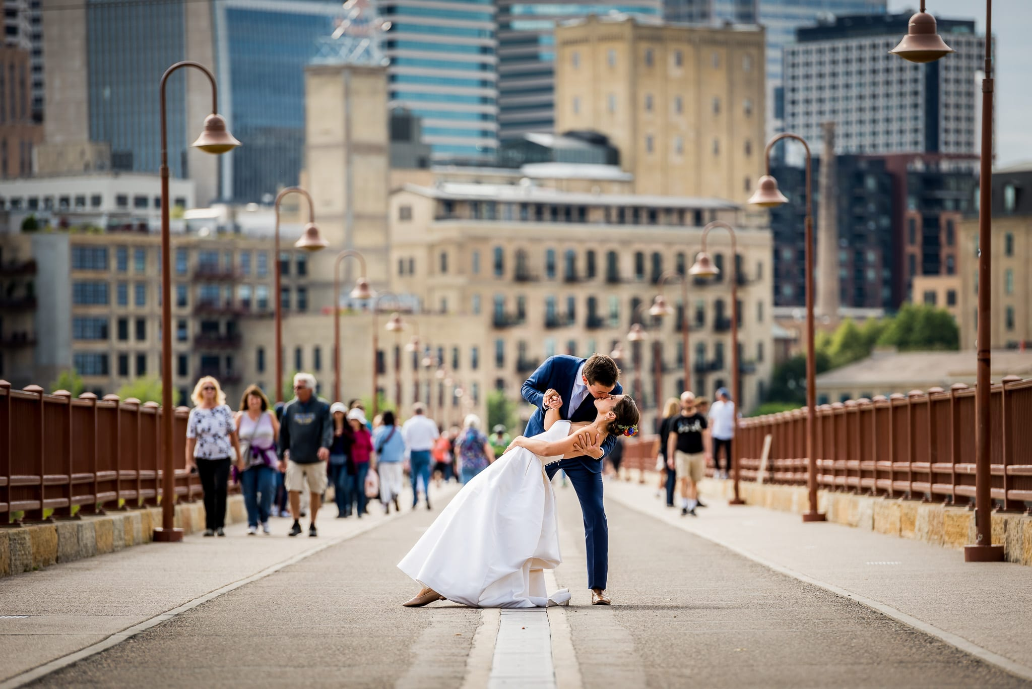 Groom kisses his bride, while he dips her, in the middle of the Stone Arch Bridge during their Nicollet Island Pavilion Wedding