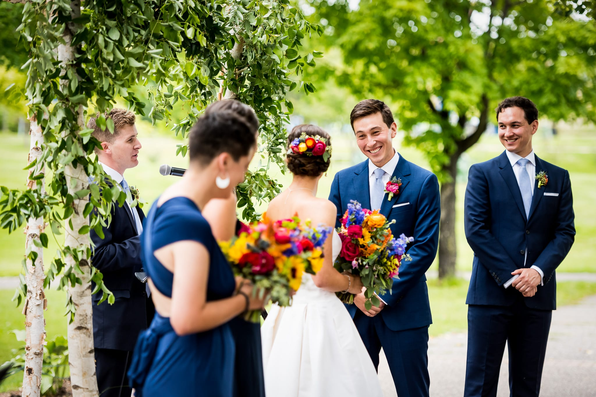 groom with massive smile while looking at his bride to be, surrounded by their wedding party