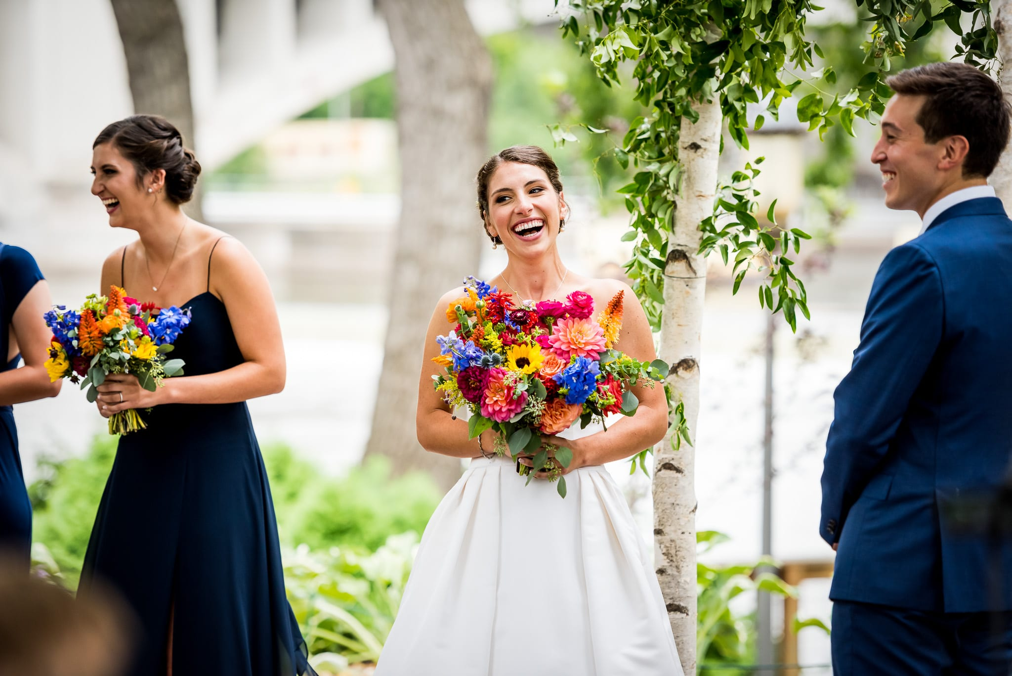 Bride laughing while she holds her beautiful flowers during her wedding ceremony at the Nicollet Island Pavilion