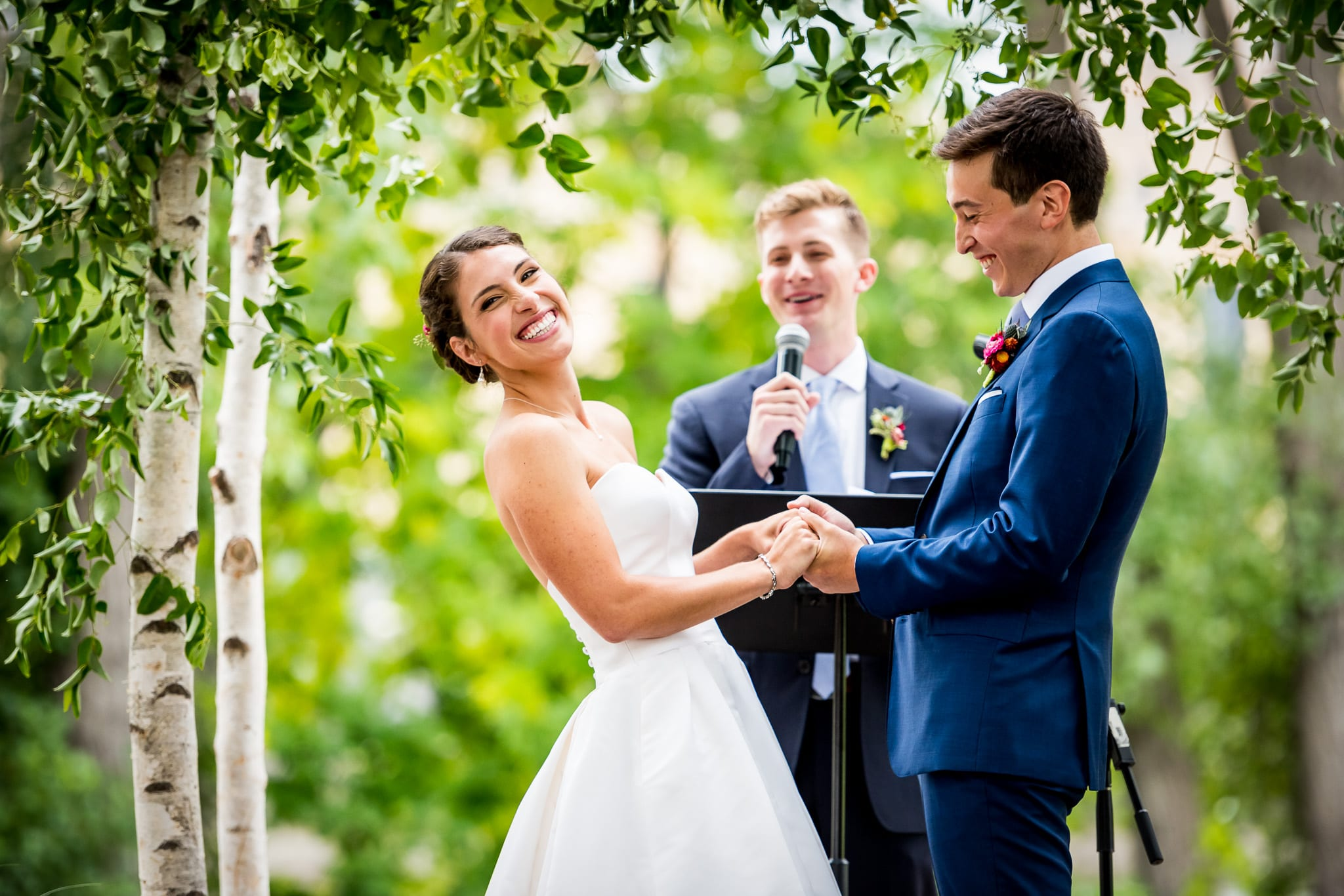 Bride up at the alter laughs out loud during her vows, while holding her grooms hands at their Minneapolis wedding ceremony