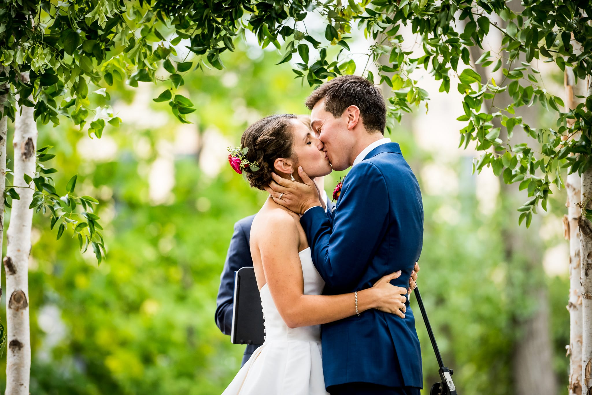 Bride and groom's first kiss during their outdoor wedding ceremony at the Nicollet Island Pavilion in Minneapolis