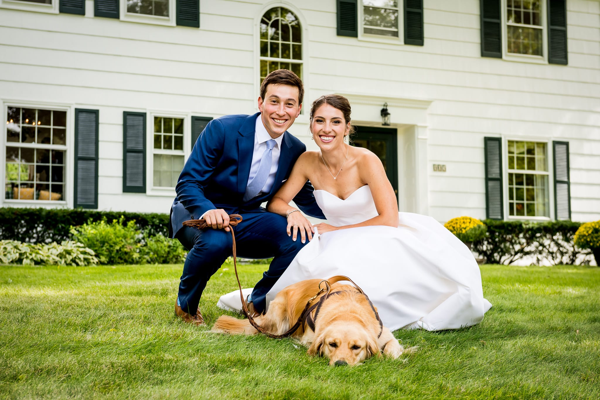 Bride and groom smiling for the camera along with their golden retriever