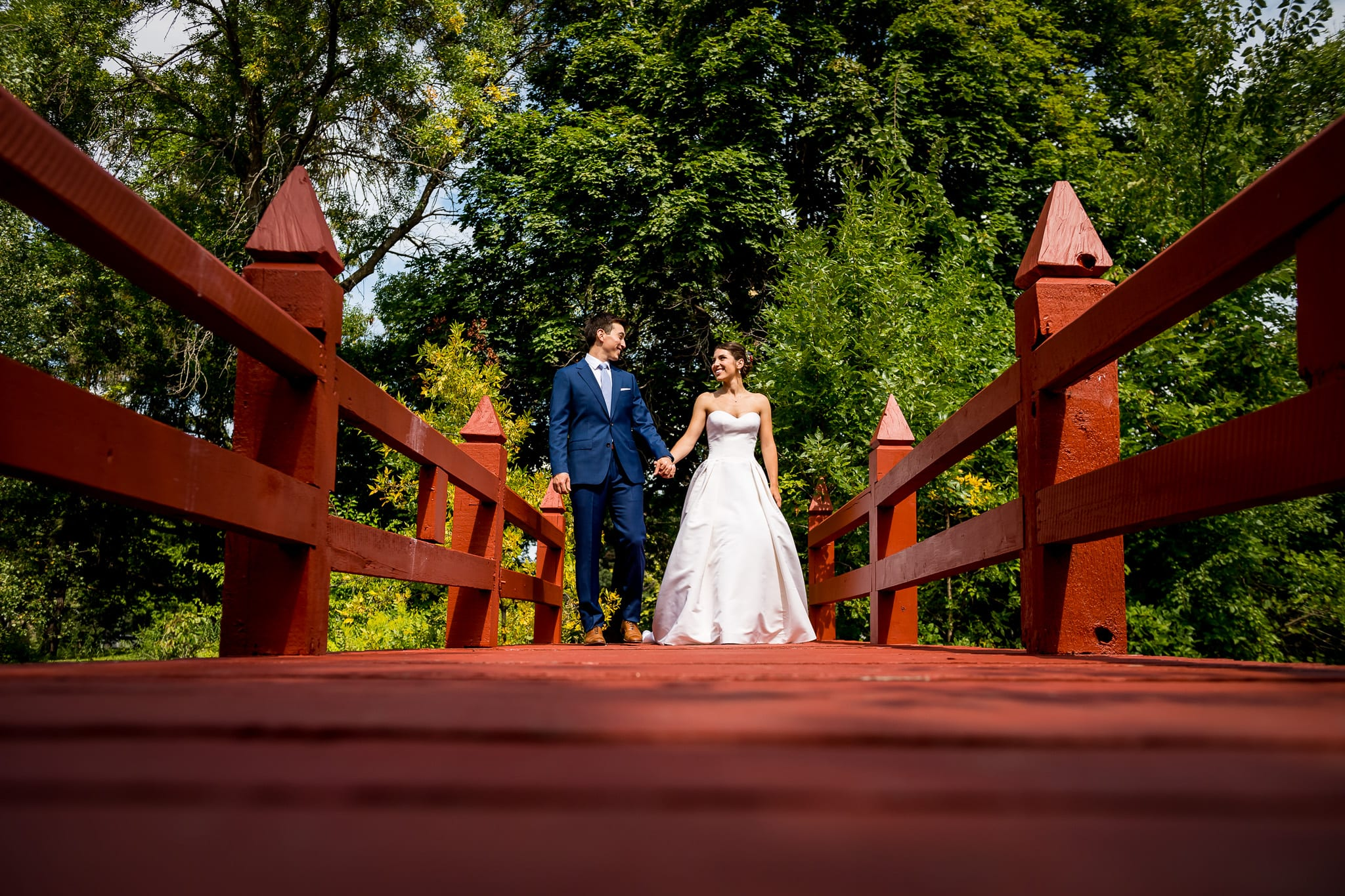 Bride and groom hold hands on a red wooden bridge