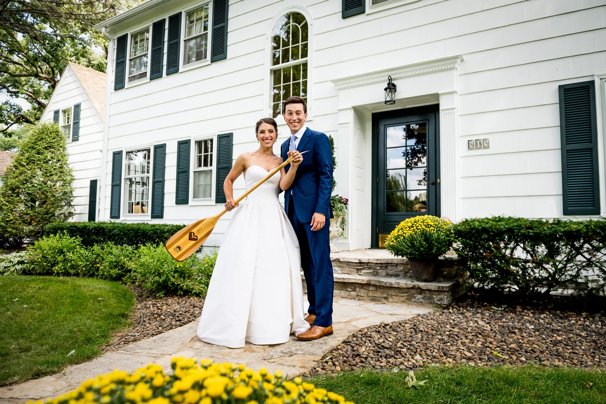 Couple poses in front of their parents home in Minneapolis on their wedding day