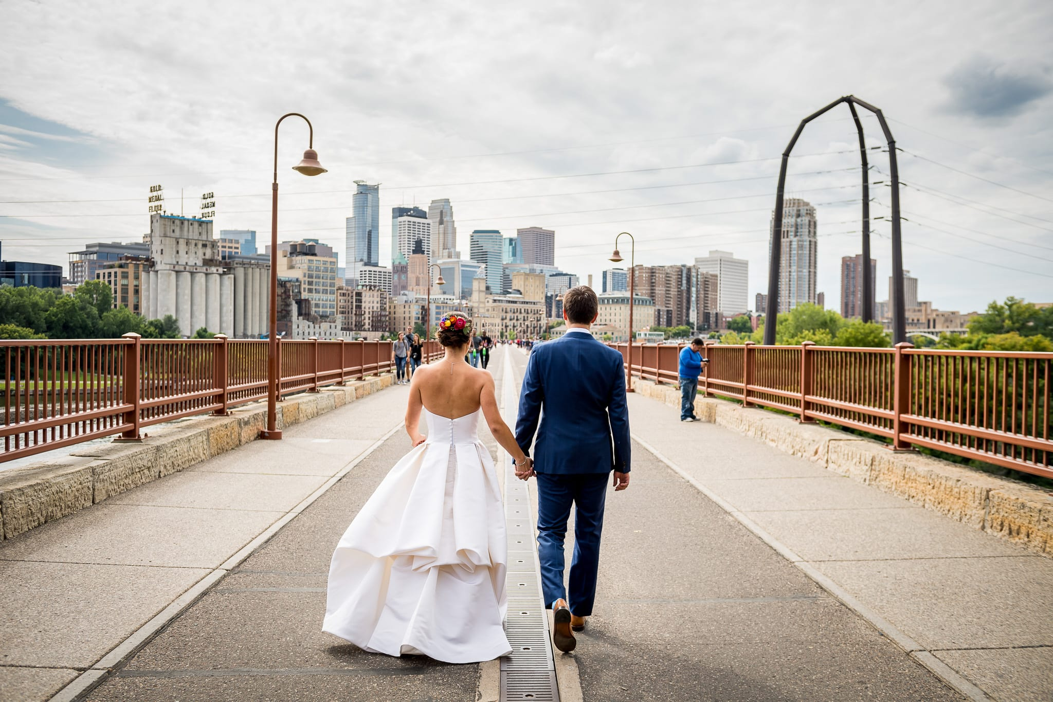 Bride and groom walking down the center of the Stone Arch Bridge with the stunning Minneapolis skyline in the background, one their wedding day at the Nicollet Island Pavilion