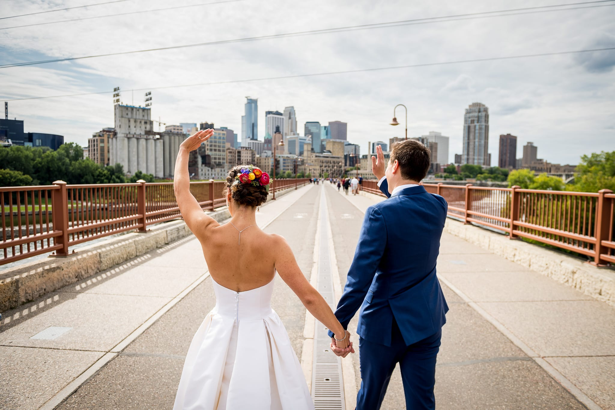 Bride and Groom wave to the Guthrie Theater from the Stone Arch Bridge on their wedding day