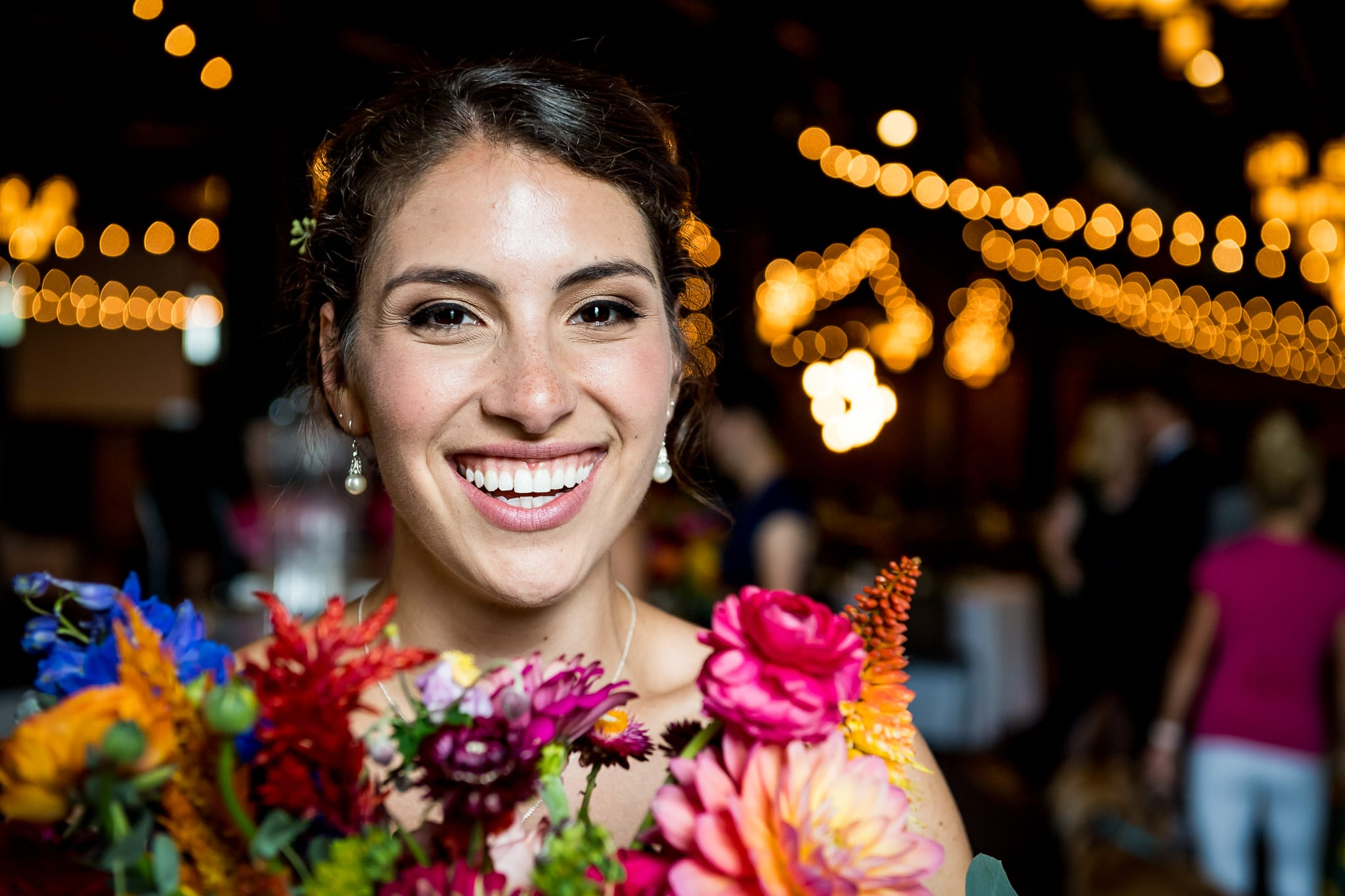 Beautiful bride smiles brightly with her flowers inside of the Nicollet Island Pavilion